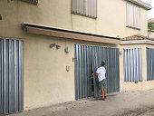 Man installing hurricane metal shutters on house door, Miramar, Florida, USA