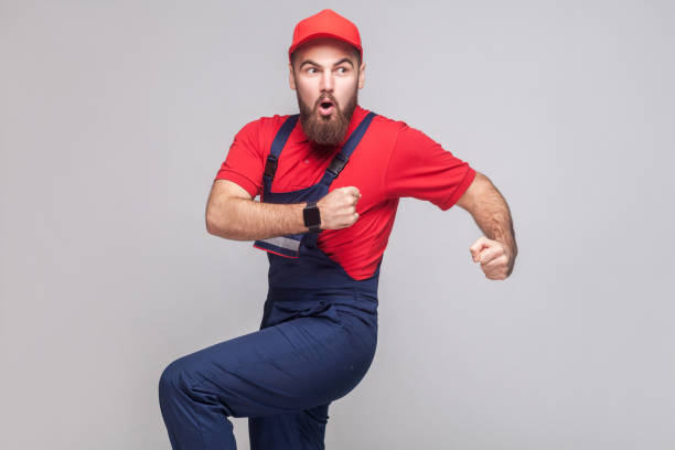Hurry up! Young amazed handyman with beard in blue overall, red t-shirt and cap are late and starting to run for help on time. stock photo