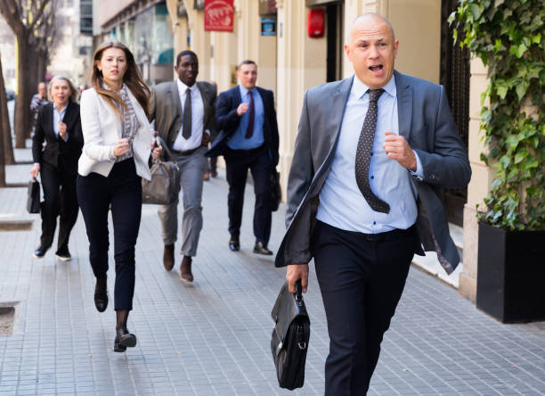 Hurrying people with stressed man in foreground Hurrying business people with stressed man in foreground running on city street beat the clock stock pictures, royalty-free photos & images