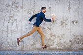 Side view of happy young man holding bouquet of flowers while running in front of the concrete wall