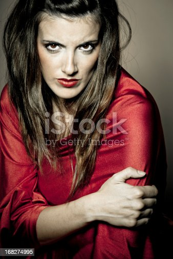 Portrait of angry woman in red dress.