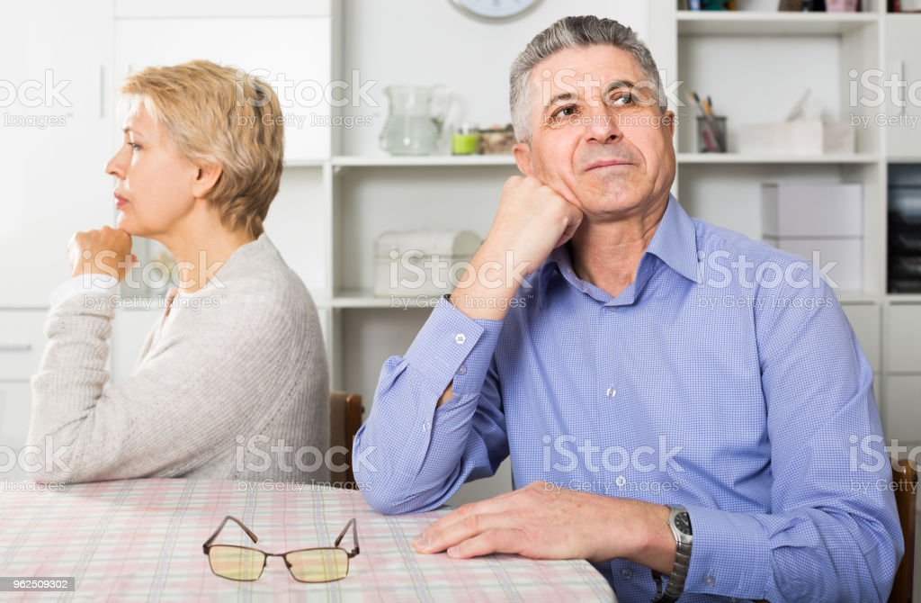 Husband and wife arguing with each other and try to resolve family conflict at table - Royalty-free Abuse Stock Photo