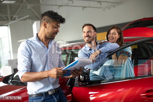 939005154 istock photo Husband and wife buying a new car together at a car dealership salon 1167575795