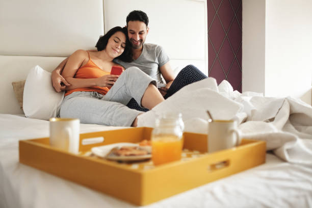 Husband And Wife Eating Breakfast In Bed Using Phone stock photo