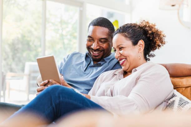 Husband and wife enjoy using digital tablet during coronavirus lockdown stock photo