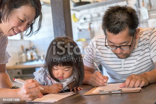 istock Husband and Wife Fill Out Paperwork While Young Daughter Watches 544581496