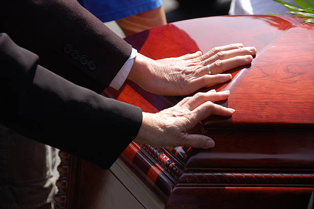 Husband and Wife Funeral Farewell 2 hands touching a closed wooden casket.  Farewell to a loved one. mourning stock pictures, royalty-free photos & images