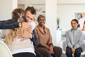 istock Husband and wife hug in group therapy session 1175358289