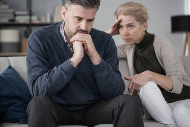 Husband and wife in therapy Worried husband and wife sitting in a marriage therapy with focus on the sad man in the foreground post traumatic stress disorder stock pictures, royalty-free photos & images