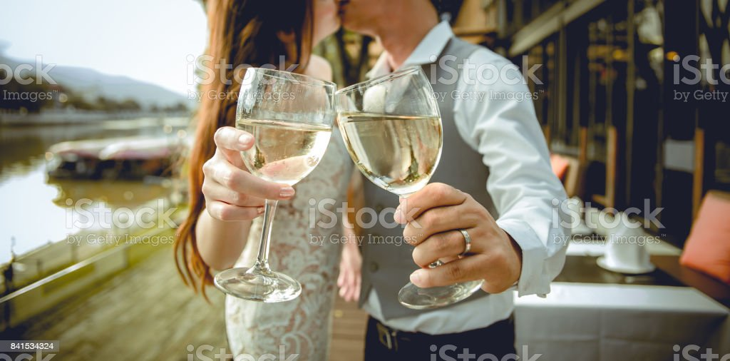 Husband and wife kiss together. There is hands holding glasses of wine in the foreground. Focus at hands holding glasses of wine. Shallow depth of field. stock photo