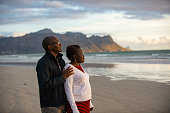 An African heterosexual mid adult couple with spectacles happily on the beach holding one another and standing together at sunset.