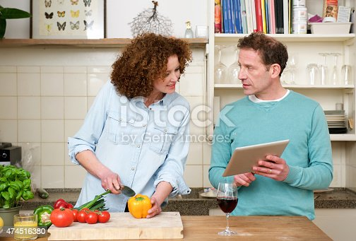 638771390istockphoto Husband and wife reading recipe from tablet 474516380