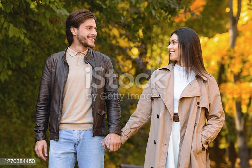 Happy husband and wife spending weekend at autumn forest, holding hands and looking at each other