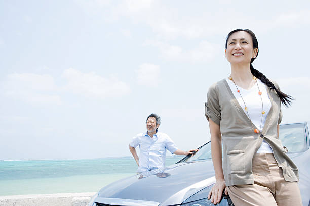 husband and wife standing on car side - asian travel in car stock photos and pictures