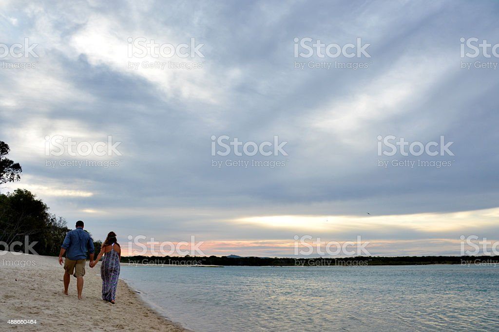 Husband and Wife walking along the beach stock photo