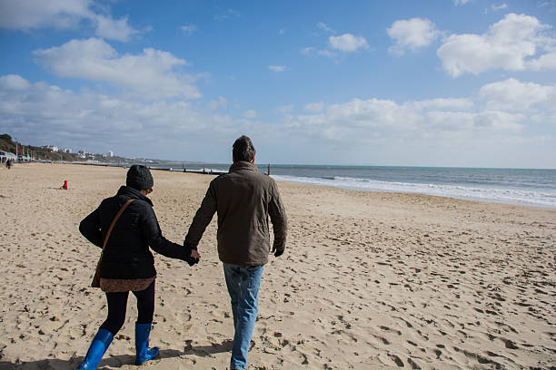 Husband and wife walking on the beach stock photo