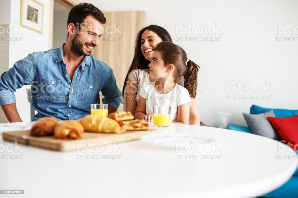 Husband and wife with they little daughter sitting at the kitchen table.Family portrait. stock photo