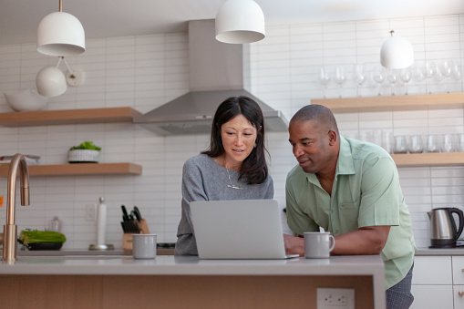 A mixed race couple use a laptop computer to pay bills online, manage budget and prepare tax documents. They are in the kitchen of their home.