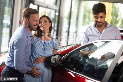 939005154 istock photo Husband buying a new car together with his pregnant wife at a car dealership salon 1171069945