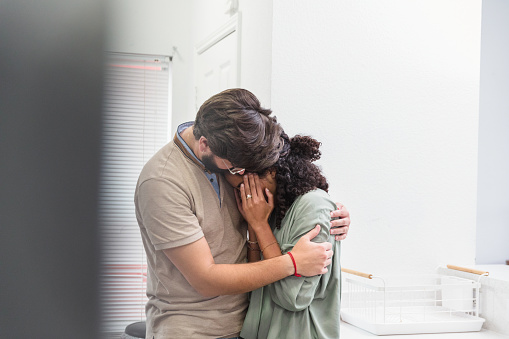 After a really hard day, the young adult husband puts his arms around his wife and comforts her.  She is stressed and has a migraine.