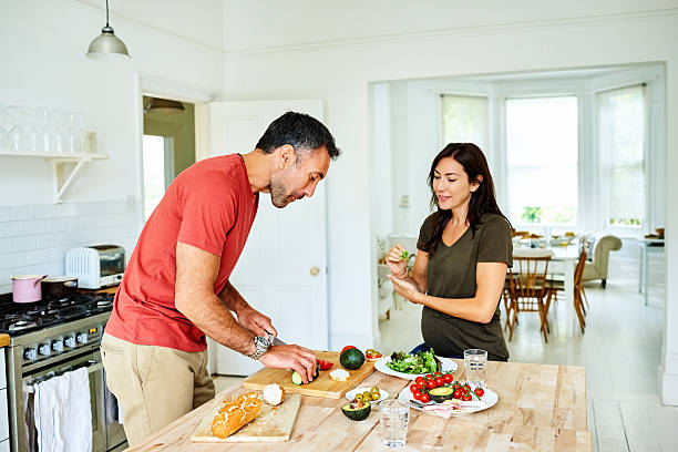 husband cooking for pregnant wife - mid adult couple stock pictures, royalty-free photos & images