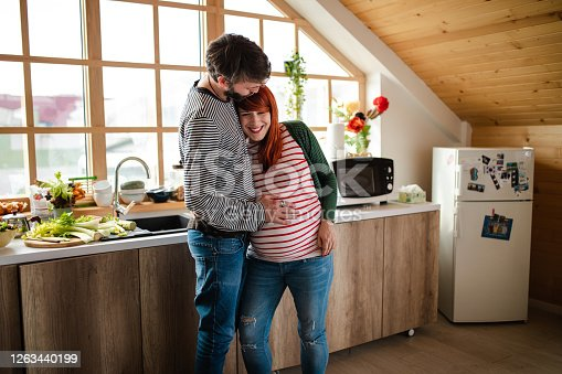 Lovely husband embracing and kissing his pregnant wife while both standing in the kitchen and showing affection
