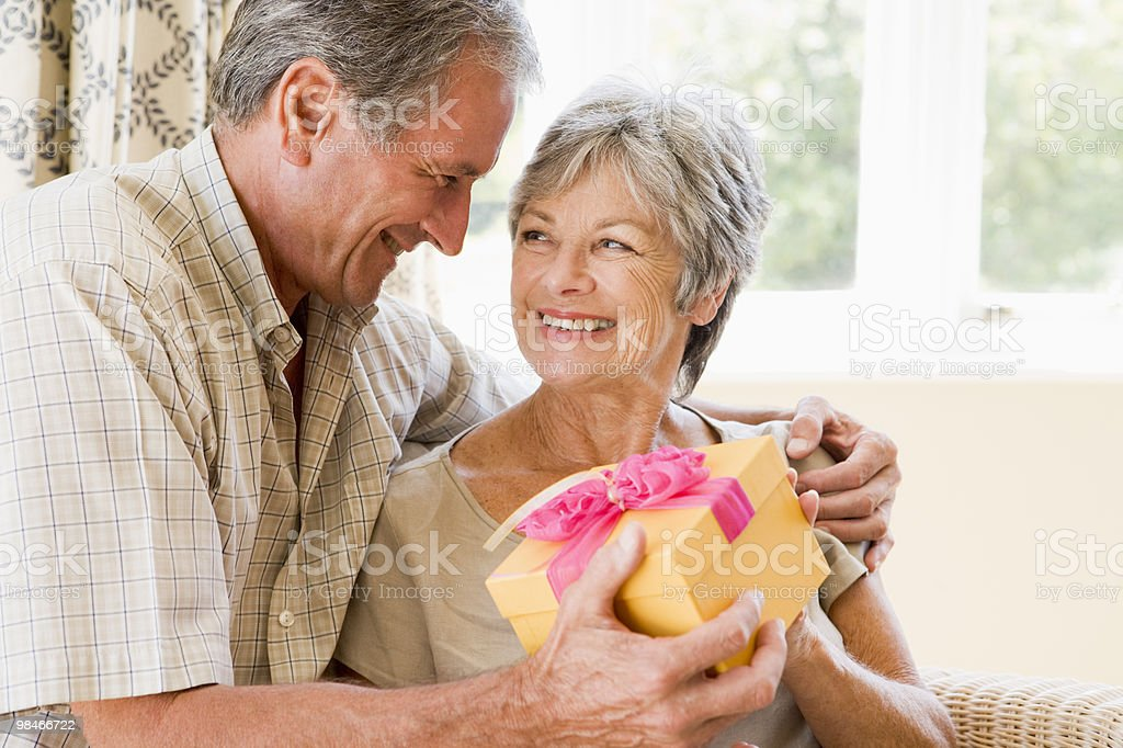 Husband giving wife gift in living room royalty-free stock photo
