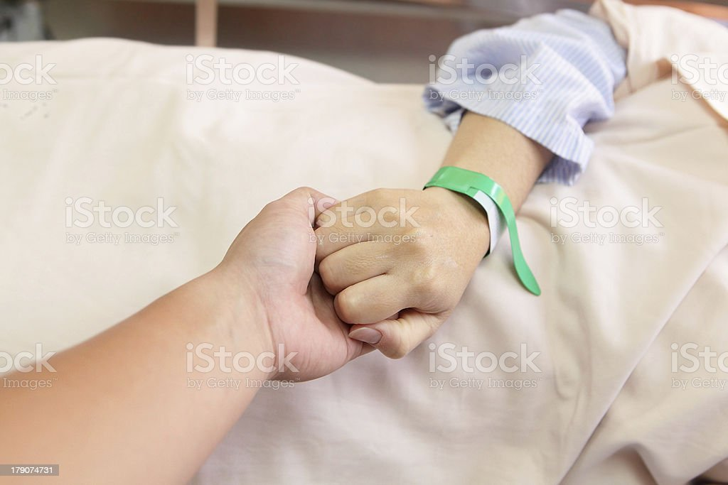 husband grip his wife's hand before surgery stock photo