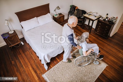 Every morning routine for senior couple. They are in pajamas in their bedroom. Husband helping his senior wife with wheelchair