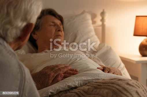 886711404 istock photo Husband holding dying wife's hand 800395026
