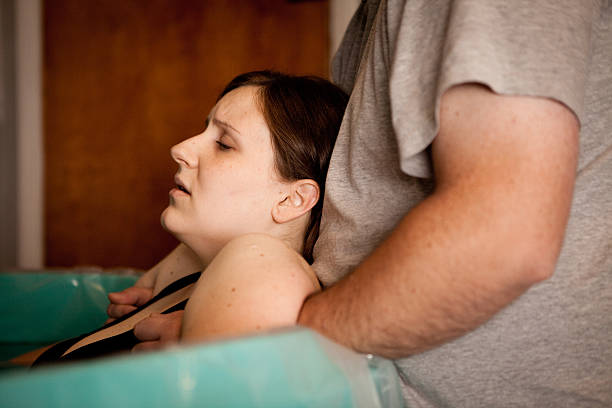 Husband Holding Wife in Labor During Home Water Birth stock photo