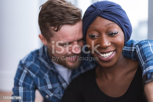 A handsome caucasian man is hugging his stunning African American wife who is recovering from cancer. They are smiling and feeling optimistic.