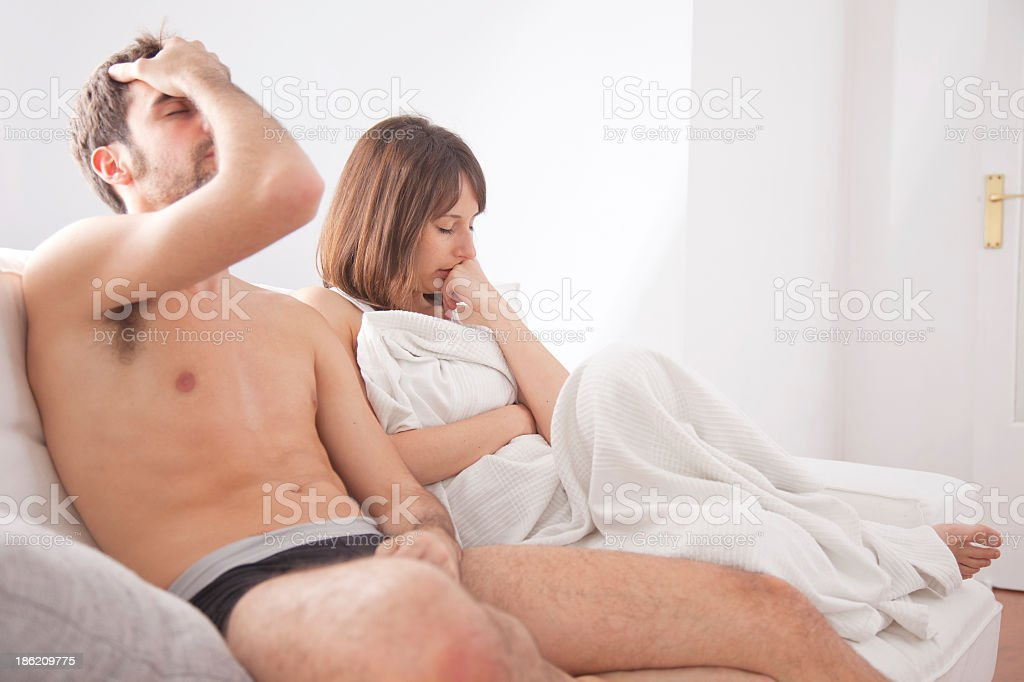 A husband in the couch having conflict problem his wife stock photo