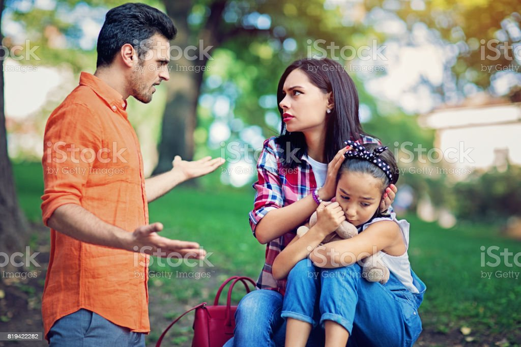 Husband is arguing with wife at the front of their little daughter stock photo