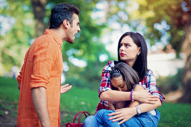 husband is arguing with wife at the front of their little daughter - fare la guardia foto e immagini stock