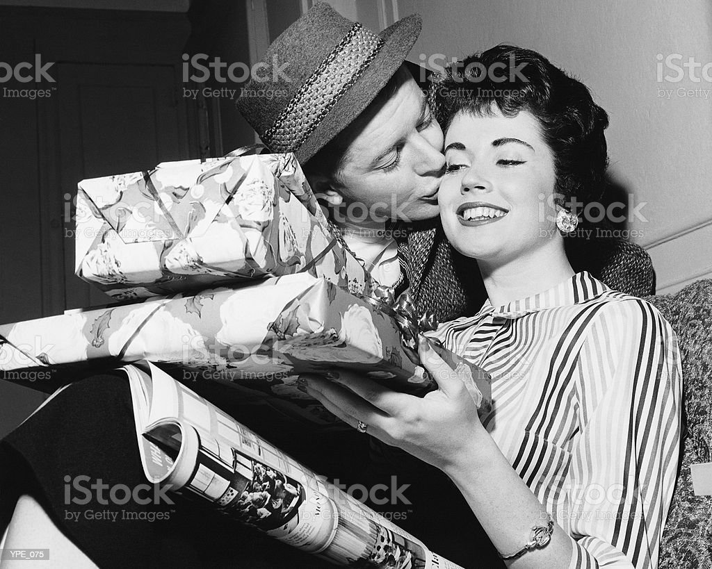 Husband kissing wife with armful of gifts royalty-free stock photo