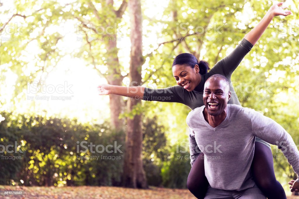 Husband laughing widely while giving a piggyback ride to his gleeful wife stock photo