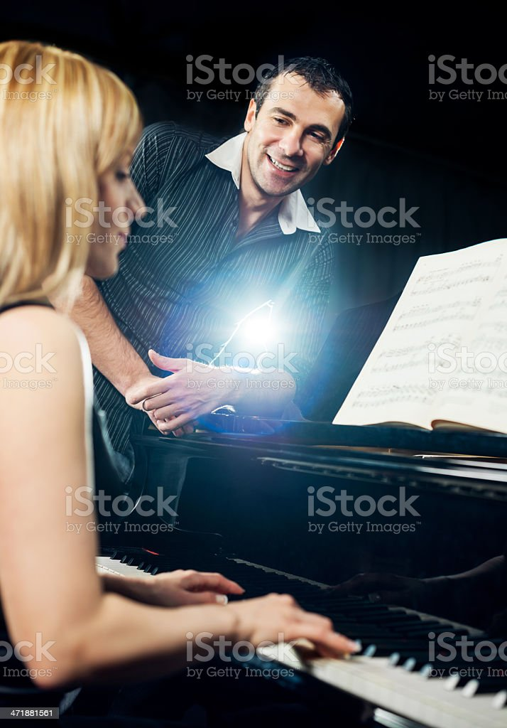 Husband listening to his wife playing the piano. royalty-free stock photo