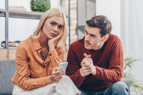 husband looking at unhappy young woman holding smartphone and looking at camera at home, relationship problem concept husband looking at unhappy young woman holding smartphone and looking at camera at home, relationship problem concept relationship difficulties stock pictures, royalty-free photos & images