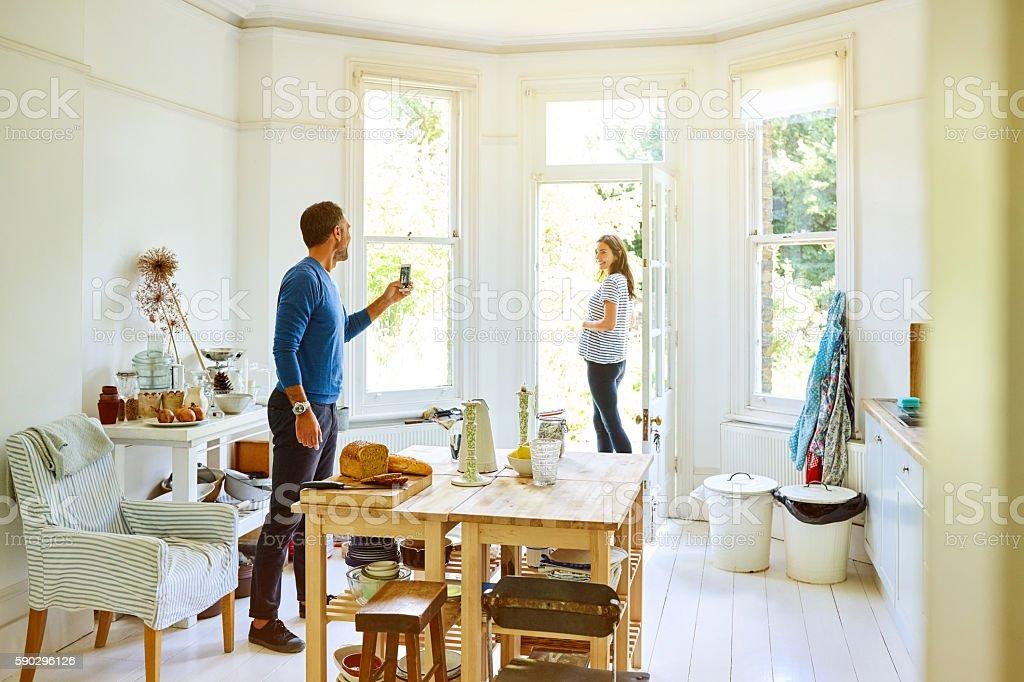 Husband photographing pregnant woman in kitchen royaltyfri bildbanksbilder