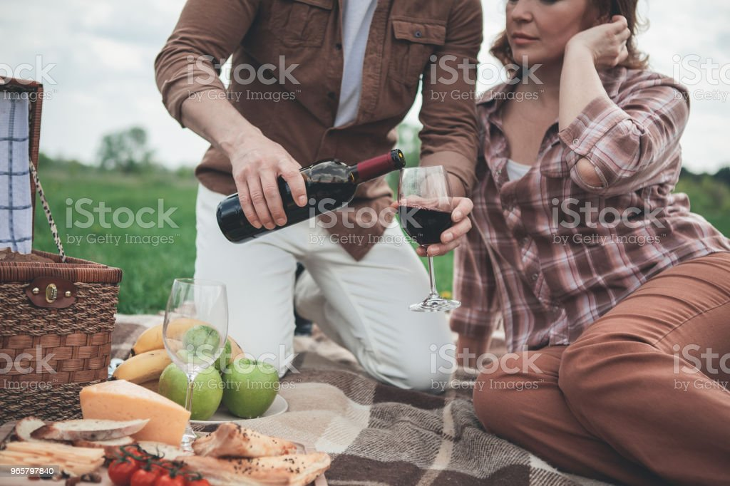 Husband pouring red wine into glass for wife during picnic - Стоковые фото Алкоголь - напиток роялти-фри