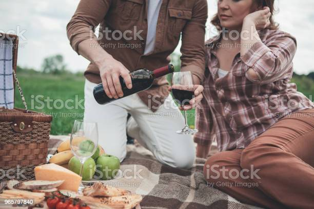 Husband Pouring Red Wine Into Glass For Wife During Picnic — стоковые фотографии и другие картинки Алкоголь - напиток