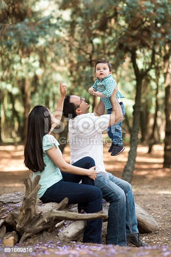 811227514 istock photo Husband sitting next to wife and picking up little boy 691669816