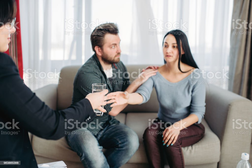 Husband soothes wife at psychotherapist reception - Royalty-free Adult Stock Photo