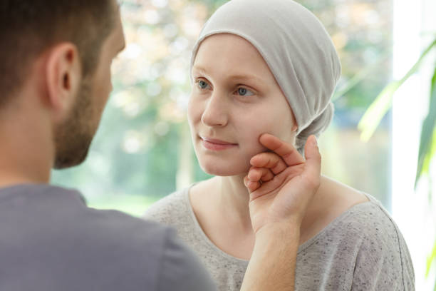 Husband stroking ill wife's face Husband stroking ill wife's face supporting her in cancer relapse chemotherapy cancer stock pictures, royalty-free photos & images