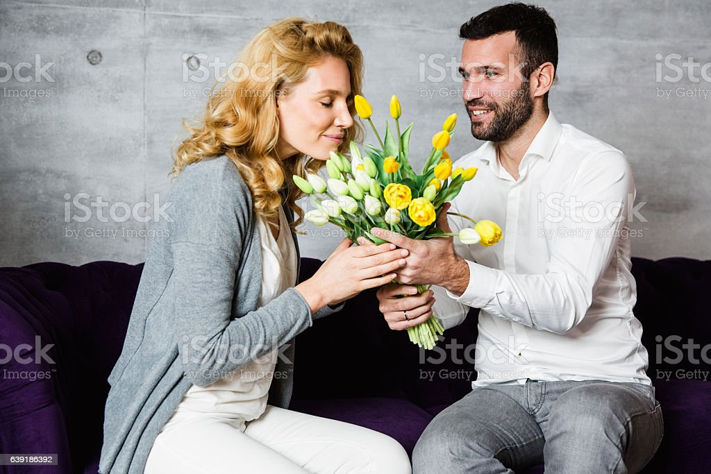 Husband surprising his wife with flowers stock photo