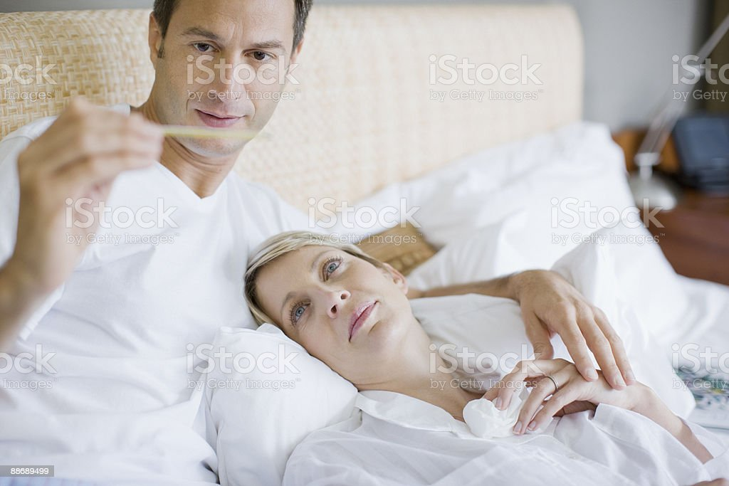 Husband taking wifes temperature royalty-free stock photo