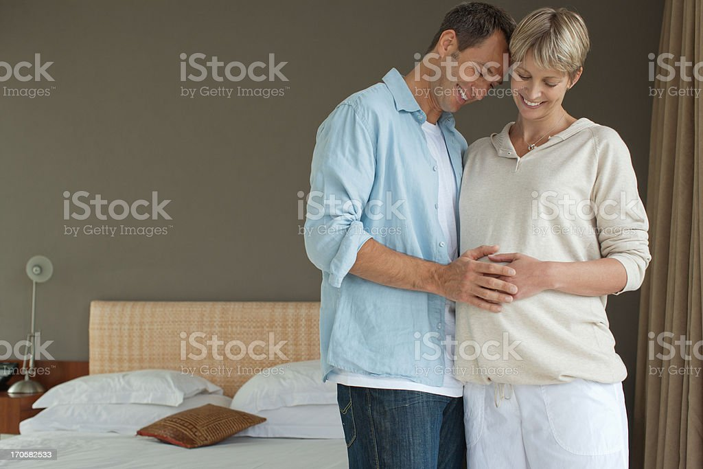 Husband touching pregnant wife's stomach royalty-free stock photo