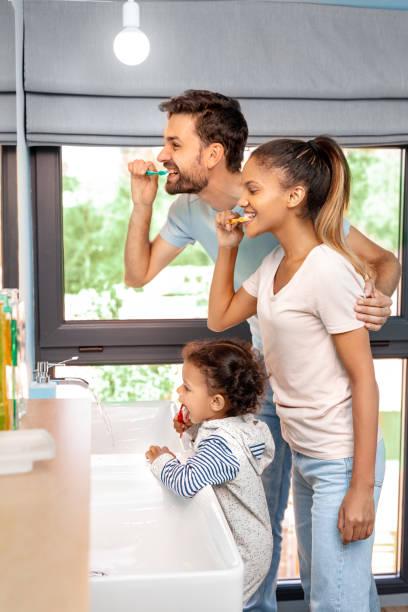 Husband, wife and kid girl brushing teeth in bathroom stock photo