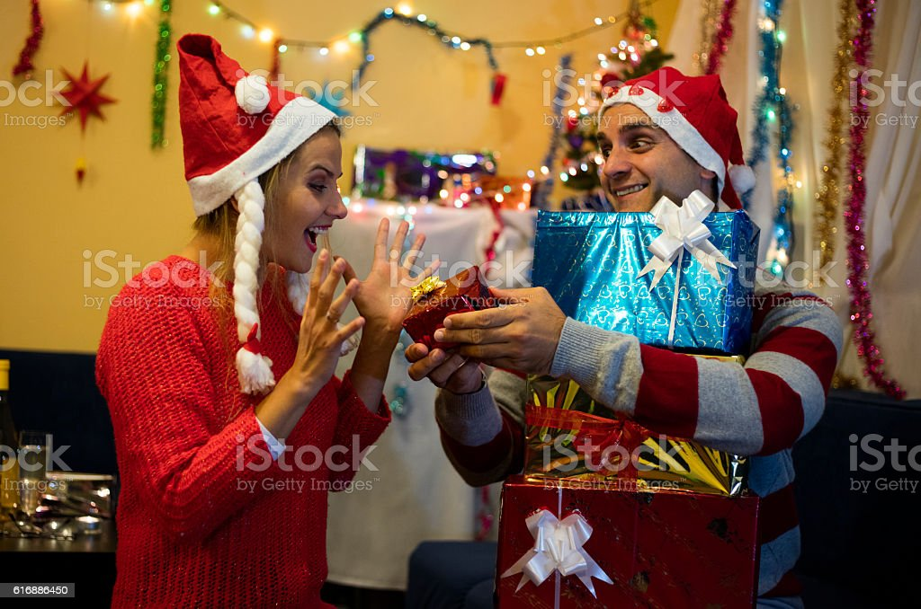 Husband with gifts surprised his happy wife. Happy New Year. stock photo